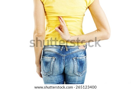 Close up of crossed fingers behind a woman's back.  Isolated on white background - stock photo