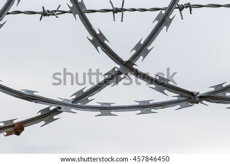 Close up of crossed pieces of corroded razor and barbed wire on white background - stock photo