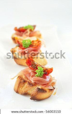 Close up of crostini with parma ham and sun dried tomatoes - stock photo