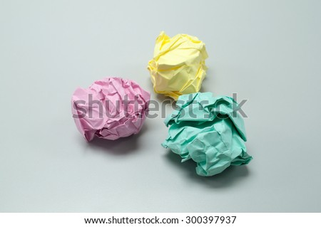 Close up of crumpled colored paper ball on white table background