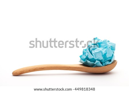 close-up of crumpled paper ball,  blue wadded paper on spoon