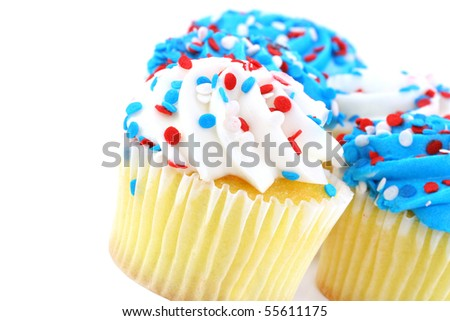 Close up of cupcakes decorated in patriotic red, white and blue.  On white with copy space. - stock photo