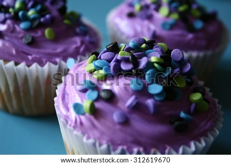 Close up of cupcakes with purple frosting and sprinkles - stock photo