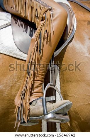Close up of custom horse back riding chaps with fringe. - stock photo