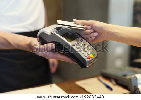 Close up of customer paying by credit card  - stock photo