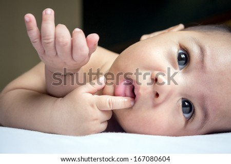 Close up of cute Asian baby boy sucking his finger on a white bed - stock photo