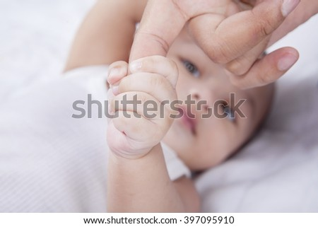 Close up of cute baby boy holding fathers hand while lying on the bed - stock photo