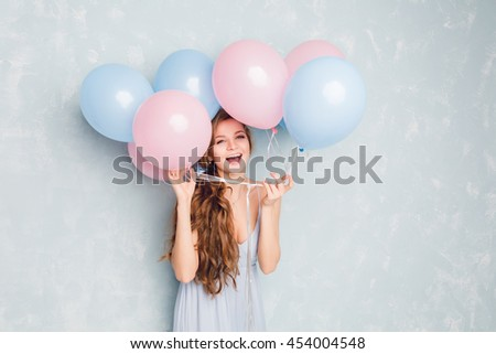 Close-up of cute blond girl standing in a studio, smiling widely and playing with blue and pink baloons. She wears light blue dress and has braided hair. She is having fun. - stock photo
