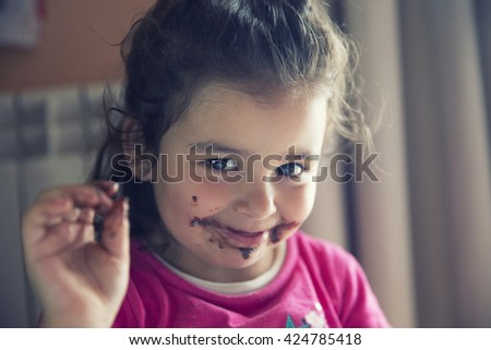 Close-up of cute girl with dirty mouth after eating chocolate - stock photo