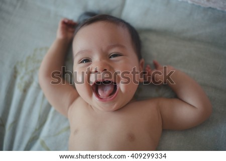 Close up of cute 10 month old mixed race baby boy lies happily on a bed. Dark natural indoor tones, window lighting only - stock photo