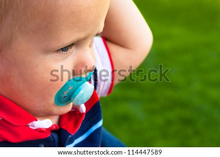 Close up of cute toddler over green natural background.