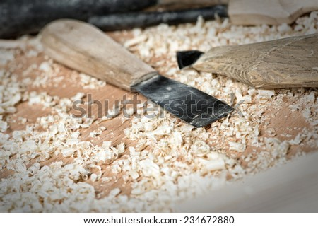 Close up of cutters for wood lying among sawdust - stock photo