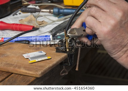 Close up of cutting a piece of iron while soldering  - stock photo