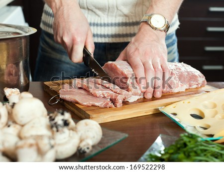 Close up of cutting raw meat - stock photo