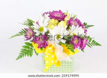 Close up of daisies and tulips arranged in a green vase with a yellow and white polka dot ribbon bow. - stock photo
