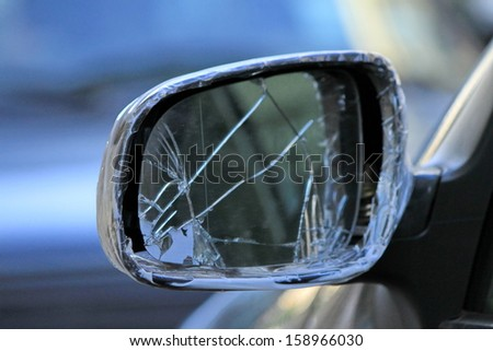 Close up of damaged rearview mirror repaired with scotch on a car - stock photo
