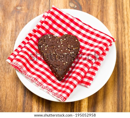 Close-up of dark chocolate and chia seed love heart cookie for healthy snack - stock photo