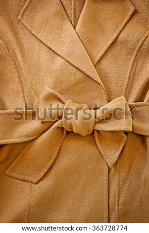 Close-up of decorative bowknot of woolen waist belt with wool coat.