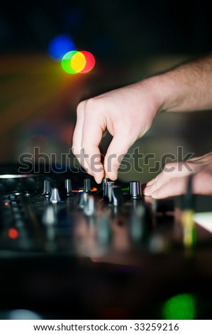 Close-up of deejays hand and control desk, soft focus - stock photo