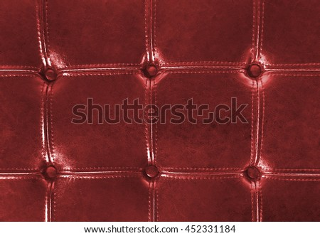 close up of deep red tufted leather upholstery with buttons - stock photo