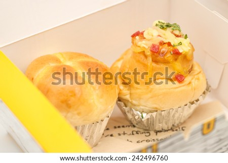 Close up of delicious and fresh baked soft bun with ham and cheese toppings in a paper box for to go or refreshment in business meeting - stock photo