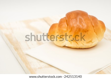 Close up of delicious and freshly baked soft bun on white paper on wood background for healthy diet  - stock photo