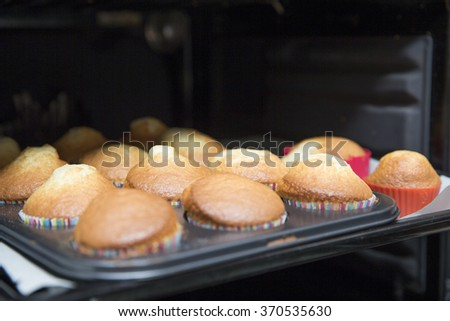 Close-up of delicious baked cupcakes in opened oven - stock photo