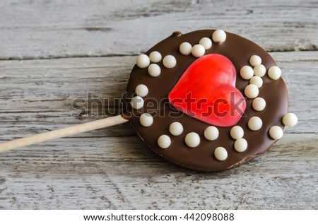 Close-up of delicious chocolate lollipop with red jelly in shape of heart in wooden table - stock photo