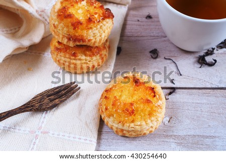 Close up of delicious coconut custard tarts on a napkin with tea cup. - stock photo