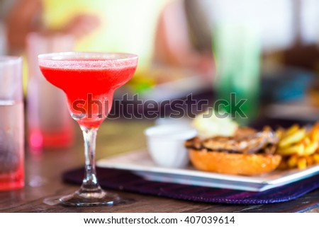 Close up of delicious fresh burger with tasty cocktail - stock photo