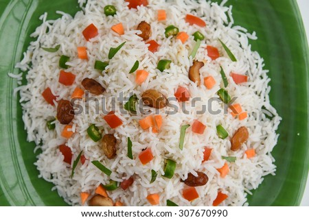 Close up of Delicious Indian Pulav / pilaf / fried rice,tomato in green plate Boiled white rice made of Basmati  rice, vegetable, nuts or meat,chicken.garnished with herbs - stock photo
