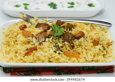 Close up of delicious North Indian food Hydrabadi chicken biriyani, vegetable Biriyani, Chicken pulao yogurt starter. Fresh Vegetable salads. basmati rice, herbs, raitha. Ramadan Kareem,  Eid-Ul-Adha - stock photo