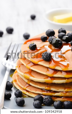 Close up of delicious pancake stack served with blueberries and flowing dripping maple syrup - stock photo