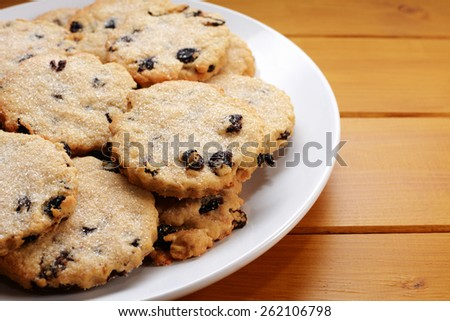 Close-up of delicious traditional Easter currant biscuits on a white plate, on a wooden kitchen table - stock photo