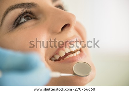 Close up of Dentist hands working attractive female teeth. - stock photo
