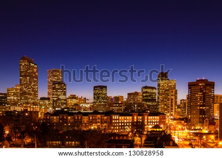 Close up of Denver Colorado skyline at dusk during the blue hour with lighted buildings and streets - stock photo
