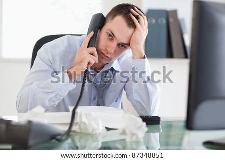 Close up of depressed and frustrated businessman on the phone