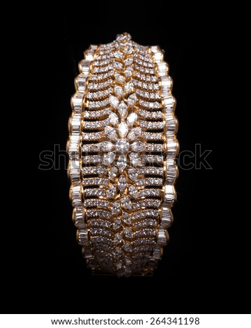 Close up of designer diamond bracelet having many diamonds over black background - stock photo