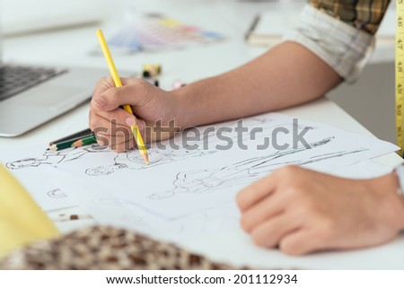 Close-up of designer drawing a fashion sketch - stock photo