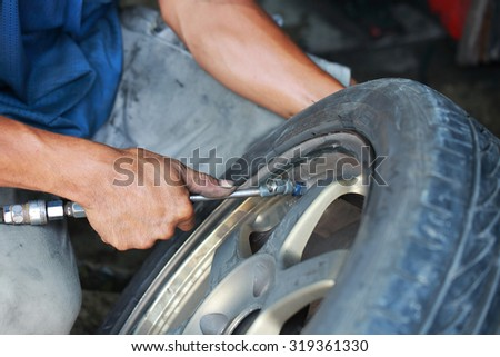 close up of Detail image of mechanic hands with tool, changing tyre of car