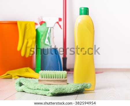 Close up of detergent bottle, mop and brush on the bright wooden floor and other cleaning supplies and equipment in background - stock photo