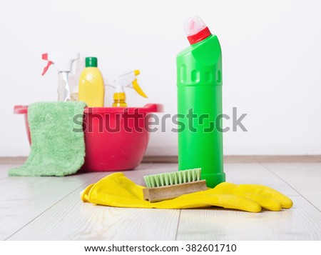 Close up of detergent bottle, rubber gloves and brush on the bright wooden floor and other cleaning supplies and equipment in background - stock photo