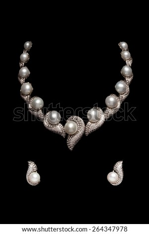 Close up of diamond necklace on black background with diamond earrings - stock photo