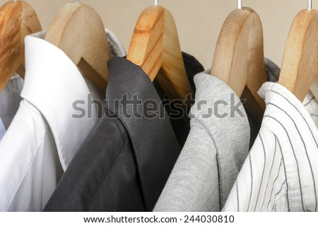 Close-up of different types of shirts on wooden hangers. Selective focus. - stock photo