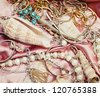 Close up of different women accessories and jewelery on pink fabric - stock photo