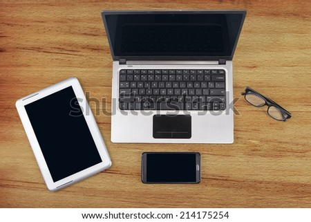 Close up of digital tablet, laptop computer, smartphone, and glasses - stock photo