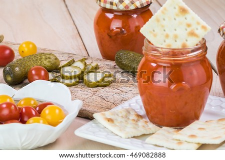 Close up of dill pickles and cherry tomatoes pickles on a cutting board and open jar with roasted red pepper spread and crackers.