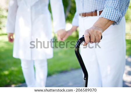 Close-up of disabled female hand holding cane with her doctor walking near by - stock photo