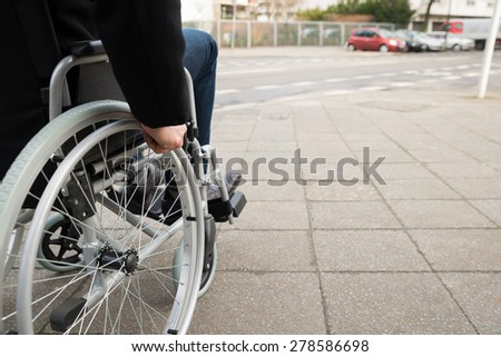 Close-up Of Disabled Man Sitting On Wheelchair - stock photo