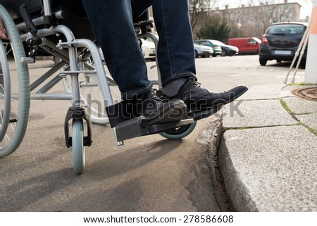 Close-up Of Disabled Man Sitting On Wheelchair On Street - stock photo